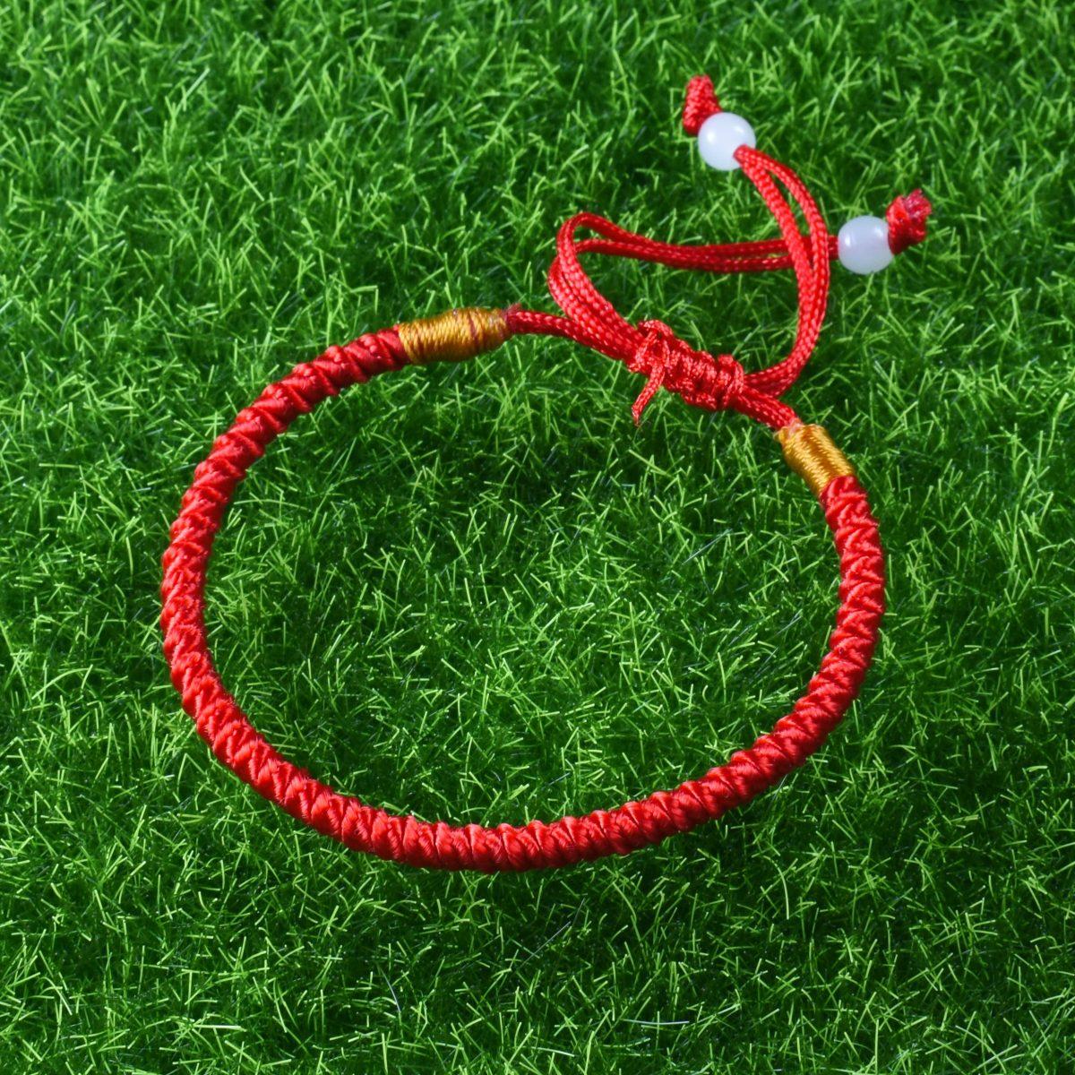Красный браслет из шнурка лежит на траве